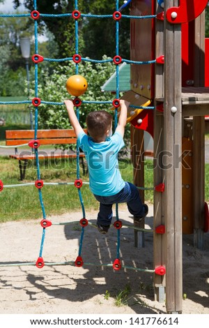 Little boy climbing on rope at playground, dangerous