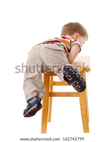 Little boy climbing on stool, isolated on white