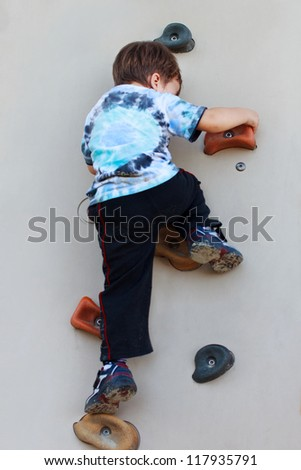 Little boy climbing on wall without rope and helmet dangerous