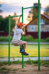 little boy climbs horizontal bar on Playground. Summer holidays. Street sports exercises. Sports, lifestyle, and healthy childhood. Happy children's portrait outdoors. a child climbs on horizontal bar