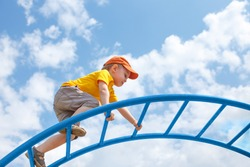 little boy climbs up the ladder on the playground. child climbs confidently up the ladder against the blue sky. copy space for your text