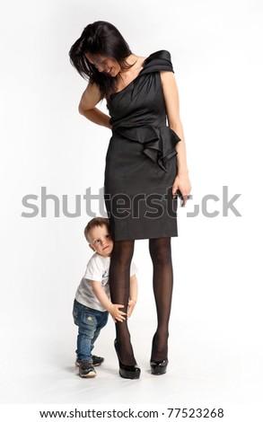 Little boy clinging to mother's leg unwilling let her go - stock photo