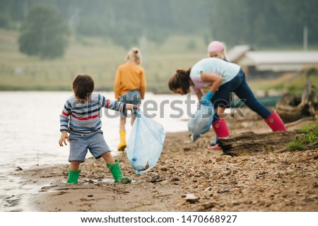 little boy collecting garbage with group of kids along the river. Eco tourism. Environmental pollution. Ecological problem. #1470668927