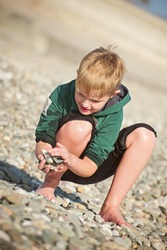 Little boy collects pebbles