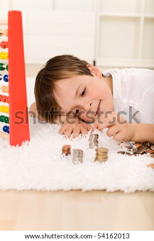 Little boy counting his money laying on the floor building coin columns