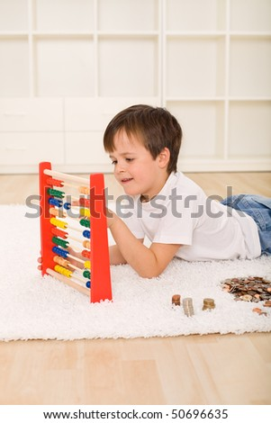 Little boy counting his savings - a pile of coins - financial education concept