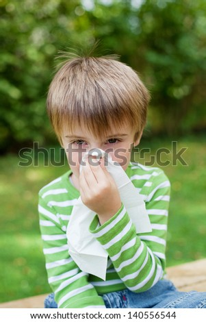 Little boy covering his nose because of allergy