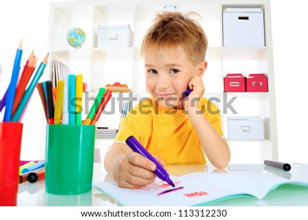 Little boy drawing in his notebook at home.