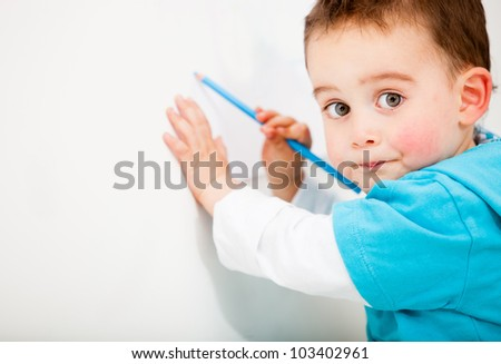 Little boy drawing on a white wall