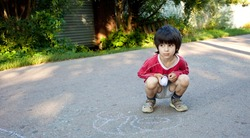 little boy drawing on gray asphalt