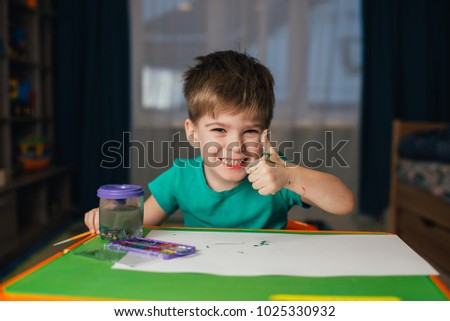 Little boy draws a brush and paint his first picture. Focus at the drawing #1025330932