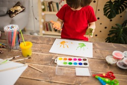 little boy draws with his hands on white paper. a little boy leaves footprints with his painted hands. Sensory development