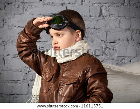 Little boy dreaming of becoming a pilot in retro style uniform - stock photo
