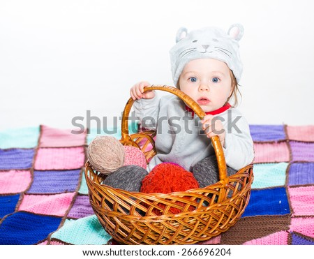 Little boy dressed as a cat sitting in basket with balls of wool