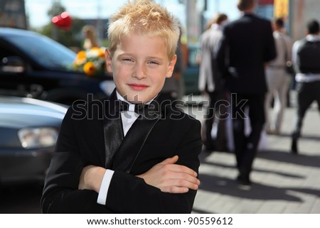 little boy dressed in tuxedo and bow tie standing at sunny day outdoor