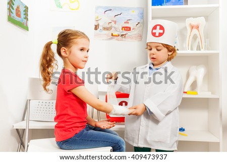 Little boy dressed like a pediatrician doctor bandaging girl's arm with a roller-bandage at the first aid room