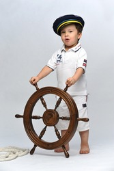 Little boy dressed up as a sailor holding the steering wheel