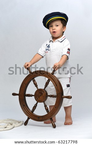 Little boy dressed up as a sailor holding the steering wheel - stock photo
