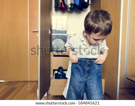 Little boy dressing and wearing his pants by himself