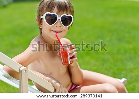 Little boy drinking juice on a lounger. A boy holding a glass of juice, big blue eyes looking at the camera