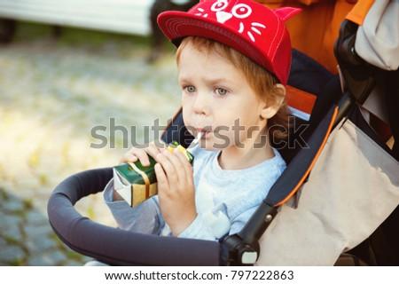 Little boy drinking juice on the street.