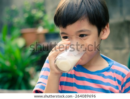 Little boy drinking milk in the park vintage color style