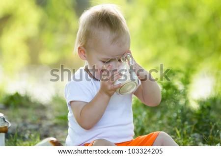 little boy drinking milk on a green grass