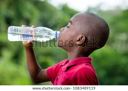 little boy drinking mineral water in nature, health concept and life of person