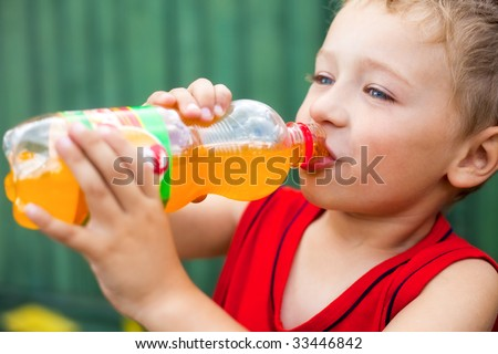 Little boy drinking unhealthy bottled soda - stock photo