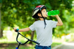 Little boy drinking water by the bike. Child in helmet riding a cycling.