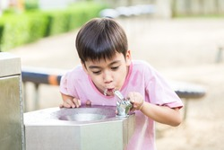 Little boy drinking water in the public park