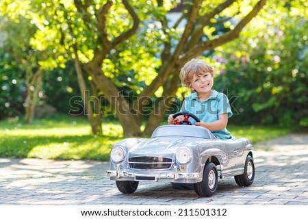 little boy driving big toy car...