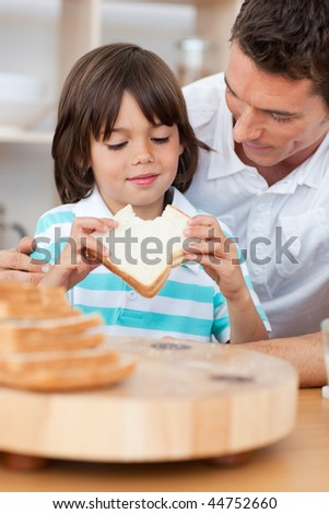 Little boy eating a sandwich with his father in the kitchen