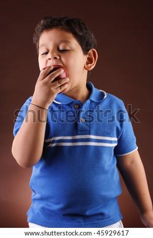 Little boy eating apple