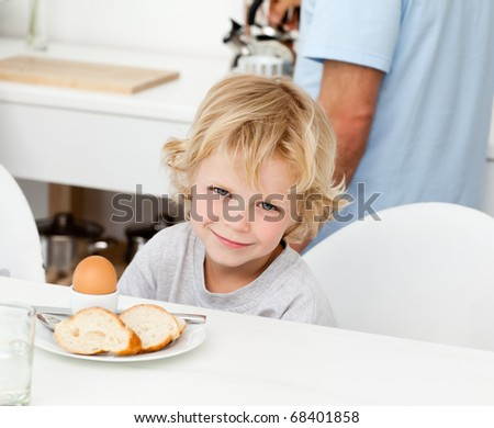 Little boy eating boiled egg and bread at breakfast in the kitchen