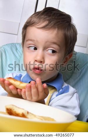 Little boy eating breakfast - stock photo