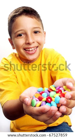 Little boy eating candy on white background. Little boy eating chicle. Little boy holding candies on white background.
