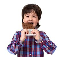 Little boy eating chocolate isolated on white