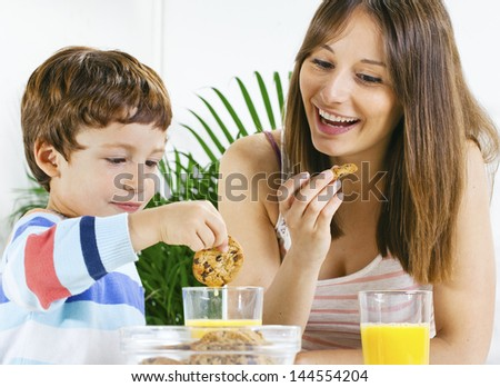 Little boy eating cookies and drinking orange juice with her mum./ Mother and son having breakfast.