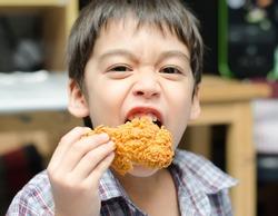 Little boy eating fried chicken