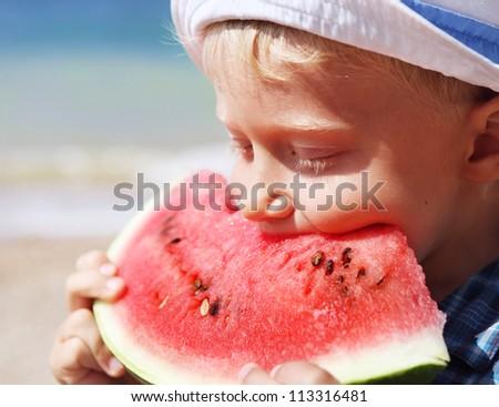 Little boy eating juicy watermelon piece