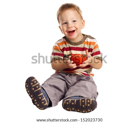 Little boy eating tomato, isolated on white - stock photo