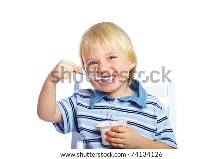 Little boy eating yogurt isolated on white background