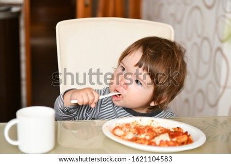 Little boy eats food from a fork in a cafe. A little boy eats food from a fork in a cafe. Family holidays, mom and son relax in a restaurant, drink cocoa and eat cake.