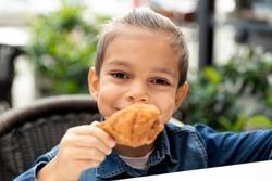 little boy eats fried chicken