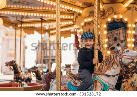 Little boy enjoying his ride at carousel in amusement park