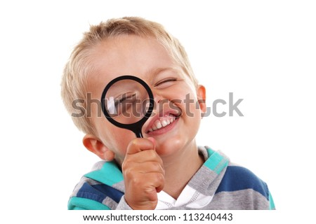 Little boy exploring with magnifying glass on white background