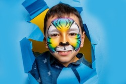Little boy face with aquagrim on face, birthday tiger makeup or party grim isolated on blue background.