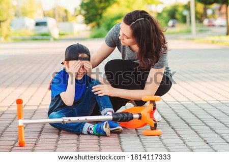 Little boy falled down while learning to ride scooter. Child crashing from scooter and crying. Mother runs to help son stand up. Falling scooter accident Stock photo ©