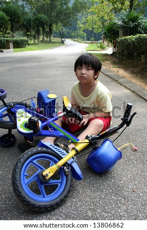 Little boy falling off bicycle sitting on the ground